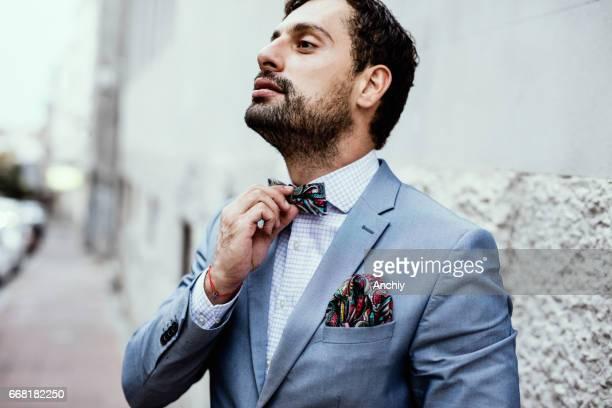 hombre ajusta la corbata de lazo - solapa camisa fotografías e imágenes de stock