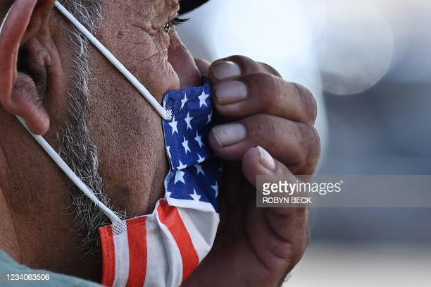 Man adjusts his American flag face mask on July 19, 2021 on a street in Hollywood, California, on the second day of the return of the indoor mask...