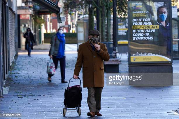 Man adjusts his face mask as he walks through Hull city centre on November 13, 2020 in Hull, England. Hull recorded 726.8 new cases per 100,000...