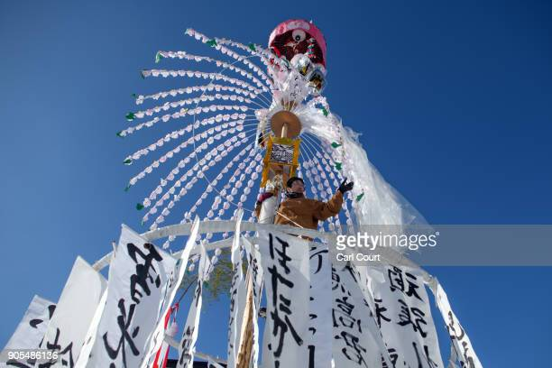 A man adjusts his family totem pole or 'Hatsuakarikago' during preparations for the Nozawaonsen Dosojin Fire Festival on January 15 2018 in...