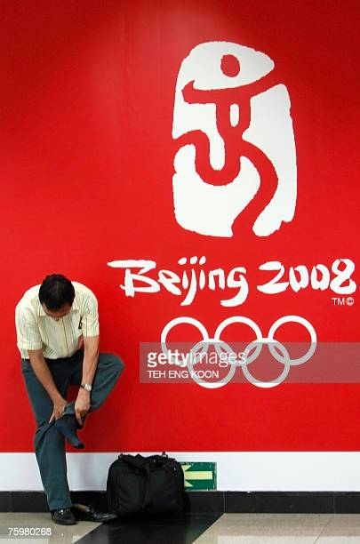 A man adjusts his sock in front of the Beijing 2008 Olympic games displayed at a subway station in central Beijing 06 August 2007 Handing out spit...