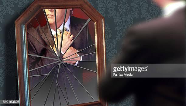 A man adjusts his tie in a broken mirror 6 January 2003 AFR Photo Illustration by KARL HILZINGEER