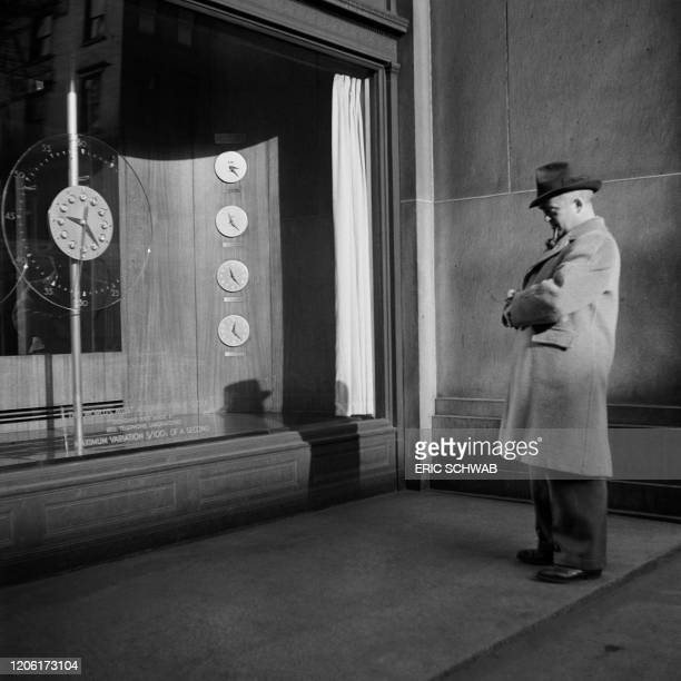 "Man adjusts his watch to the clocks displayed in the northernmost window bay of Telephone Building, AT&T headquarters, presented as ""the most..."
