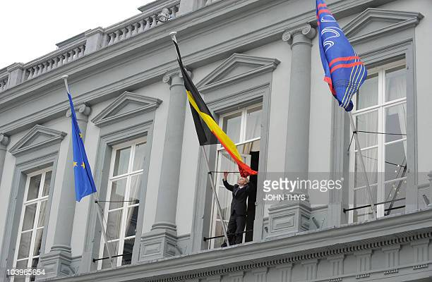 A man adjusts the Belgium flag placed on the Egdmont palace prior to the Foreign Affairs Ministers' meeting on September 10 2010 in Brussels AFP...