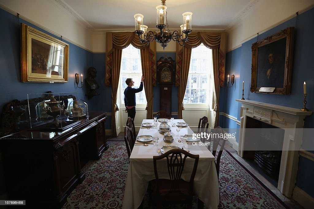 A man adjusts the decor in the Dining Room inside the Charles Dickens Museum on December 7, 2012 in London, England. The museum will re-open to the public on December 10, 2012 following a major 3.1 million GBP refurbishment and expansion programme to celebrate Dickens' bicentenary year. The museum is located in Charles Dickens' house on Doughty Street where he lived from 1837 until 1839 and in which he wrote many novels including Oliver Twist and Nicholas Nickleby.
