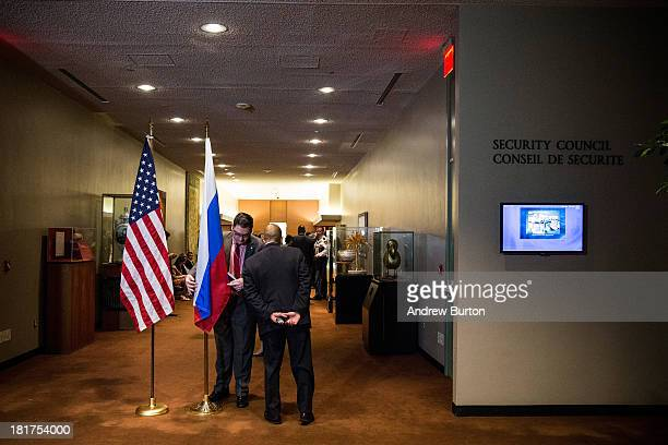 A man adjusts the Russian flag prior to a bilateral meeting between the United States and Russia during the 68th United Nations General Assembly on...
