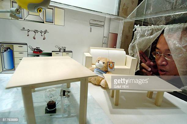A man admires a model of an indoor living room during a conference on Smart Home in Taipei 26 November 2004 The conference is organized by Industrial...