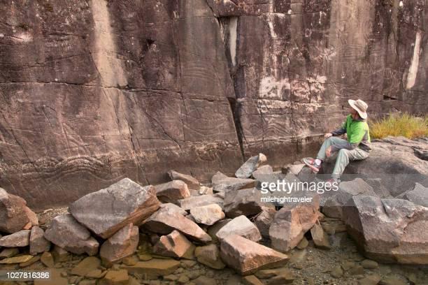Man admires First Nations rock art petroglyph Sport Lake Provincial Park Vancouver Island British Columbia
