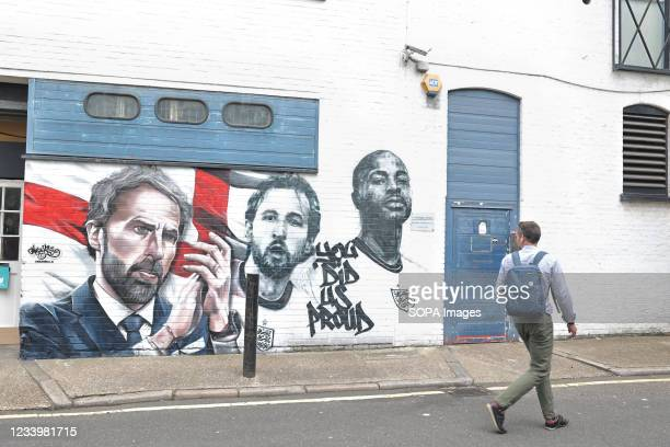 Man admires the mural of England football manager Gareth Southgate and players Harry Kane and Raheem Sterling, with the words 'You Did Us Proud', is...
