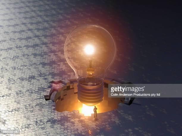 Man admiring enormous floating light bulb