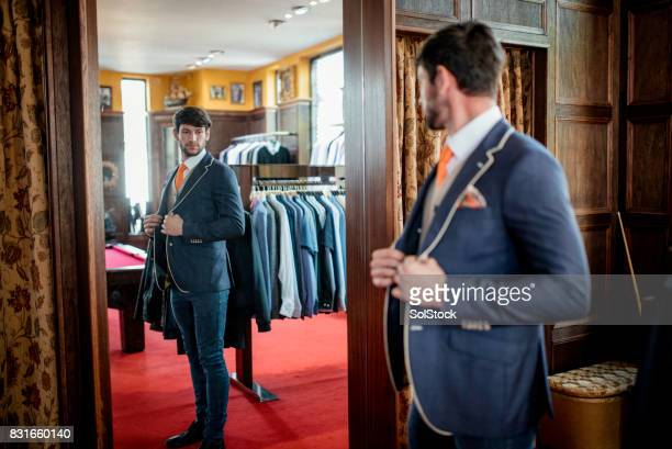 man admiring himself in a mirror in a menswear shop - men fashion stock photos and pictures