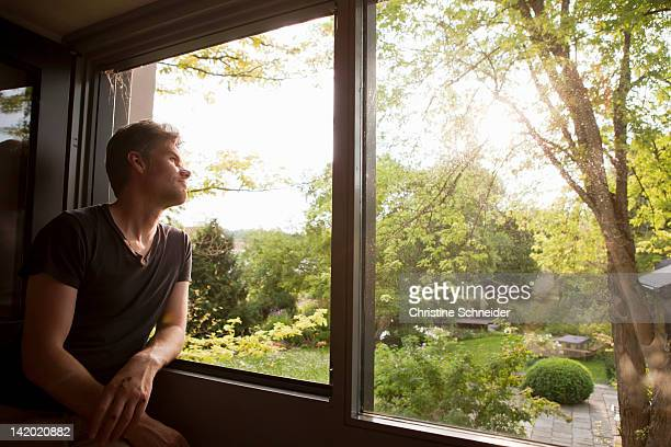 Man admiring landscape from window