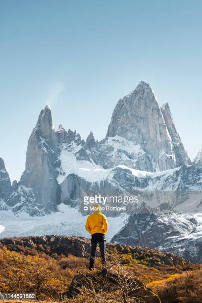 man admiring mt fitz roy, patagonia, argentina - yellow coat stock pictures, royalty-free photos & images