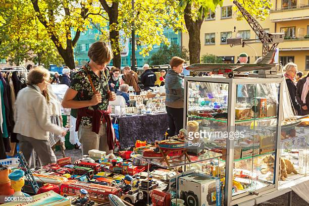 Man admiring stand with vintage tin toys on outdoor market.