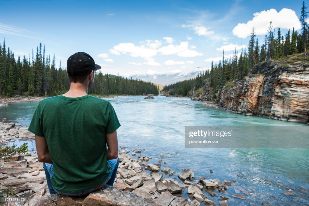Man Admiring the Athabasca River in the Canadian Rocky Mountains of Jasper National Park, Alberta, Canada : Stock Photo