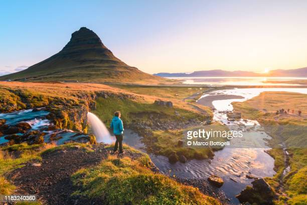 man admiring the sunrise at mount kirkjufell, iceland - islanda foto e immagini stock