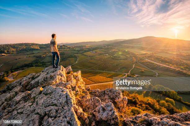 man admiring the view from the top of rock of solutre at sunset, burgundy, france - tourism photos et images de collection