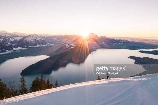man admiring the view from top of snowcapped mountain in switzerland - concepts et thèmes photos et images de collection