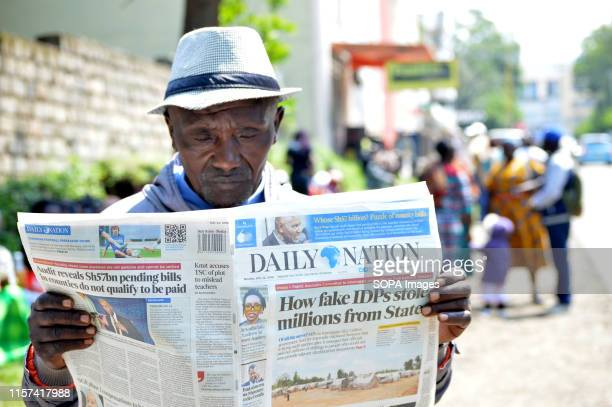 A man affected by the post poll violence reads newspapers after hearing of the main case to seek compensation was suspended pending confirmation of...