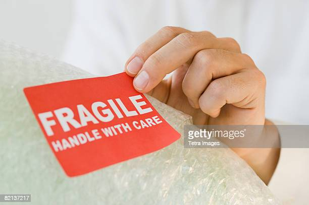 man affixing fragile sticker - fragile sticker stock pictures, royalty-free photos & images