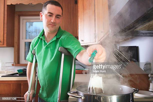 Man after anterior cruciate ligament (ACL) surgery with crutches making tea in the kitchen