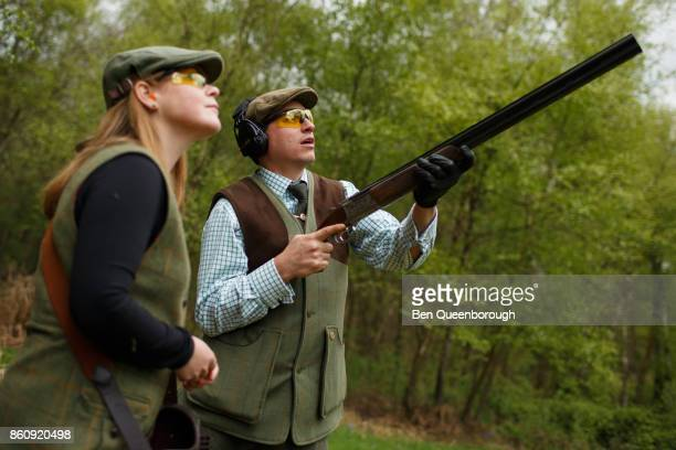 A man aiming a rifle during at clay pigeon shoot