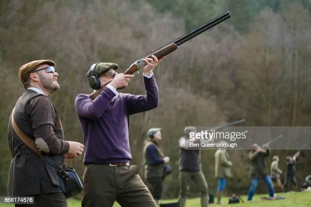 A man aiming a shot gun at clay pigeons