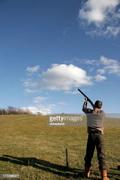 A man aiming and shooting at clay pigeons
