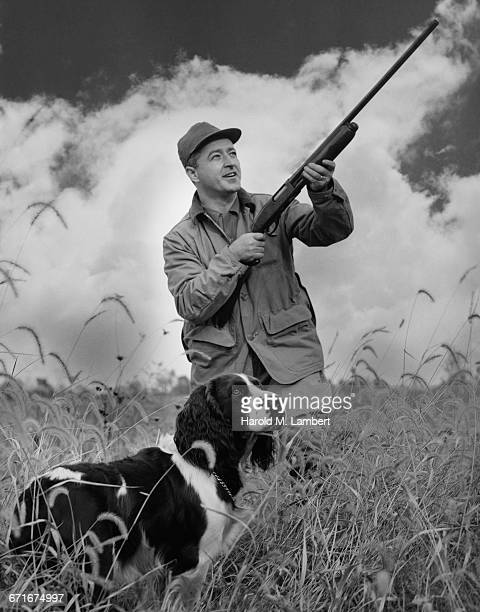 man aiming rifle along with dog  - pawed mammal stock pictures, royalty-free photos & images