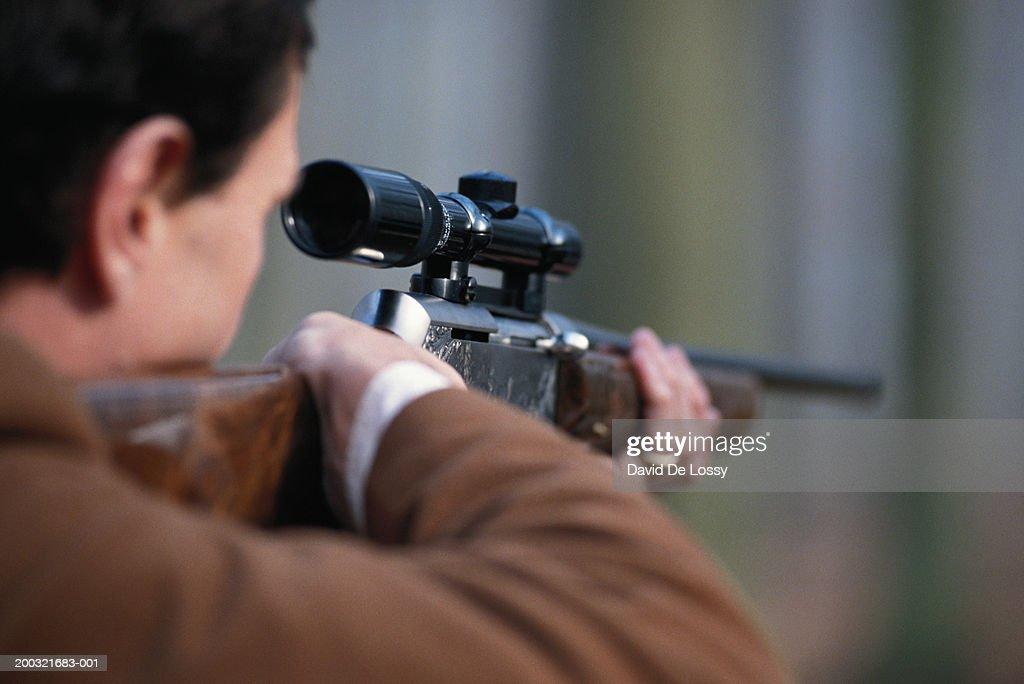 Man aiming rifle, close-up, rear view : Stock Photo