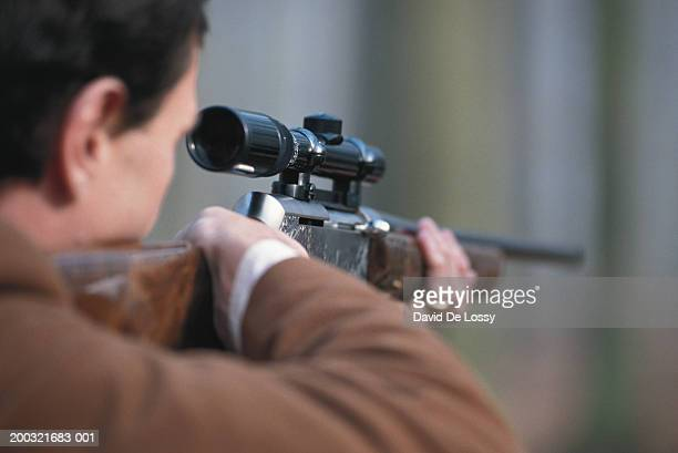 Man aiming rifle, close-up, rear view