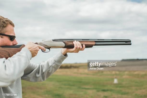 man aiming shotgun - rifle fotografías e imágenes de stock