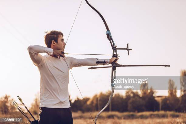 man aiming with a bow - curved arrows stock photos and pictures