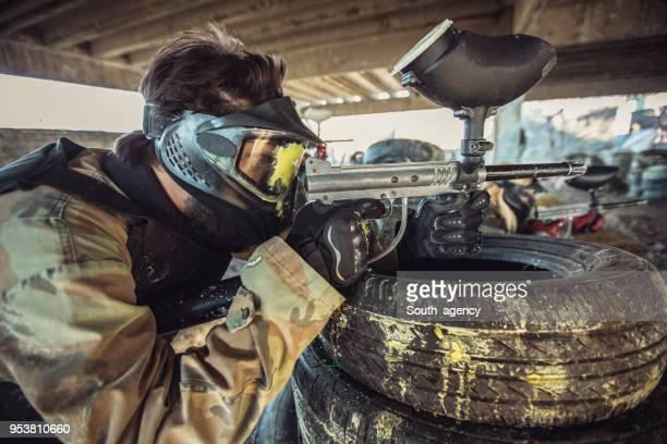 Homme qui vise avec un pistolet de paintball