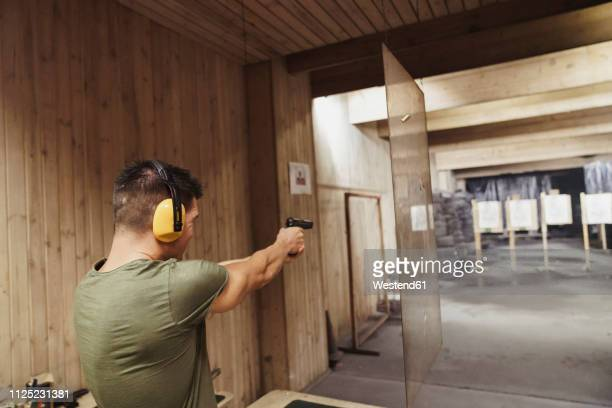 man aiming with a pistol in an indoor shooting range - target shooting stock pictures, royalty-free photos & images
