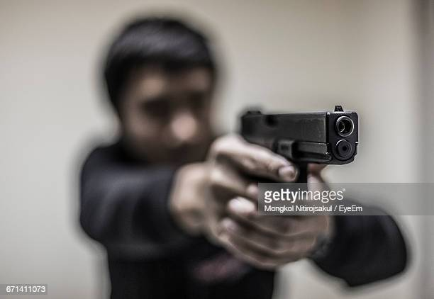 man aiming with gun against wall - pistolet photos et images de collection