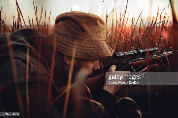 Man Aiming With Shotgun In Forest