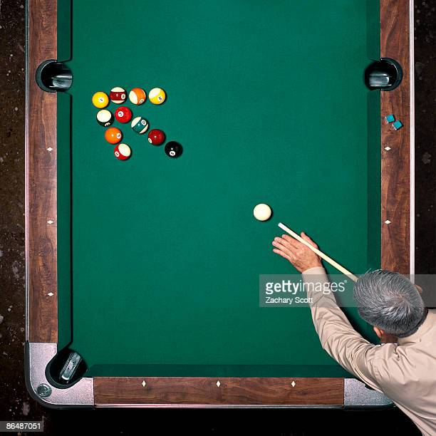 Man aims at pool balls in arrow arrangement