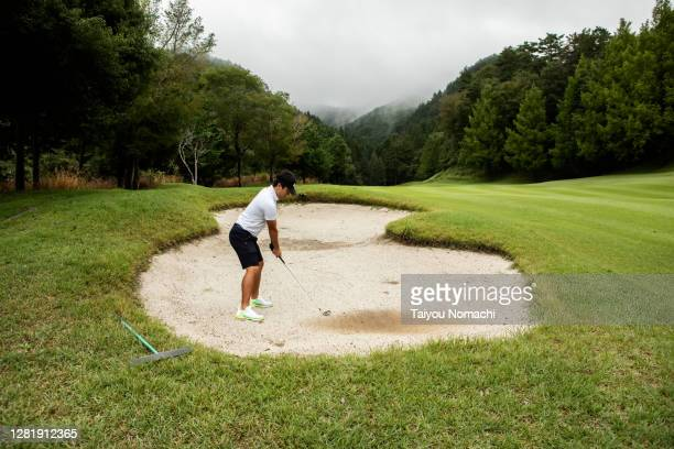 a man aims at the green from a bunker - バンカー ストックフォトと画像
