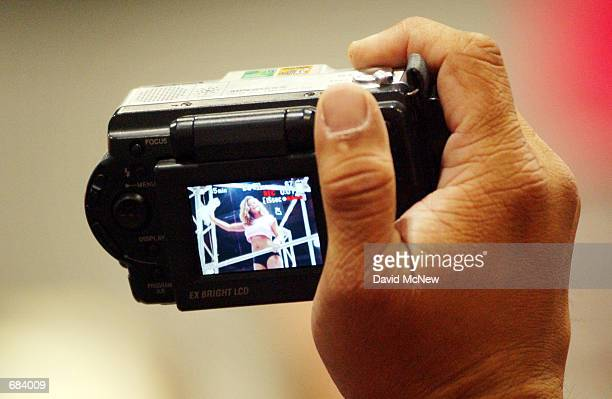 A man aims his digital camera at an exotic dancer at the Erotica LA 2002 adult industry tradeshow on June 7 2002 in Los Angeles California Attendees...