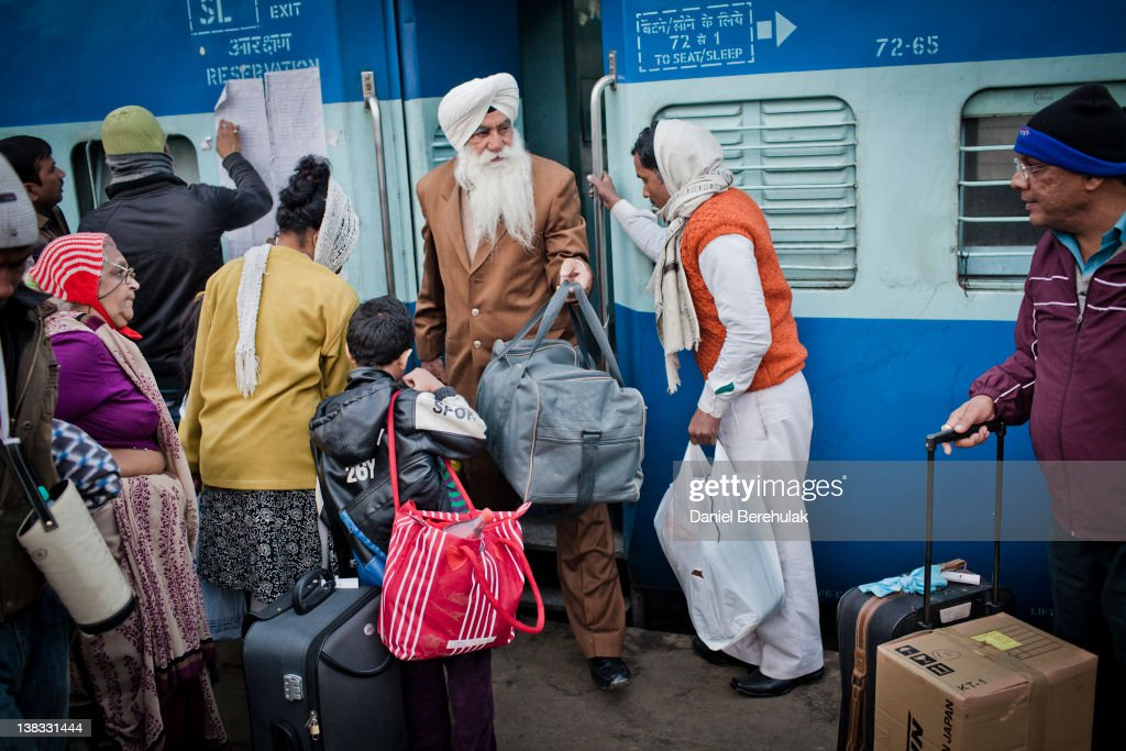 A man alights from a carriage as others wait to board the Amritsar bound train at the Nizamuddin Railway Station on February 06 2012 in New Delhi...