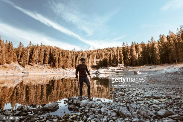man alone at carezza lake in italy