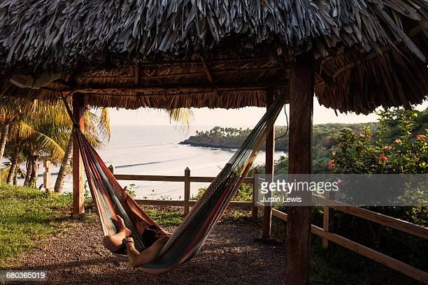 Man alone in hammock, palapa overlooking ocea