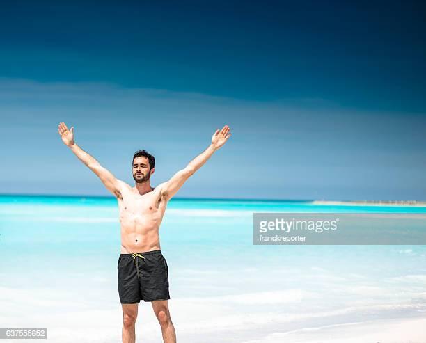 man alone in the beach praying to the sun - un solo hombre joven fotografías e imágenes de stock