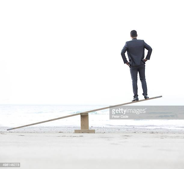 man alone on seesaw in air - seesaw stock photos and pictures