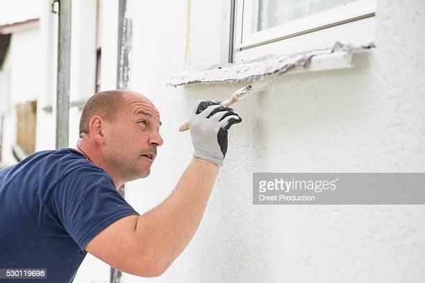 Man alone painting brush window wall house