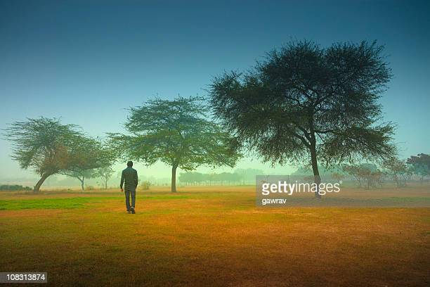 Man alone walking in park on a foggy morning