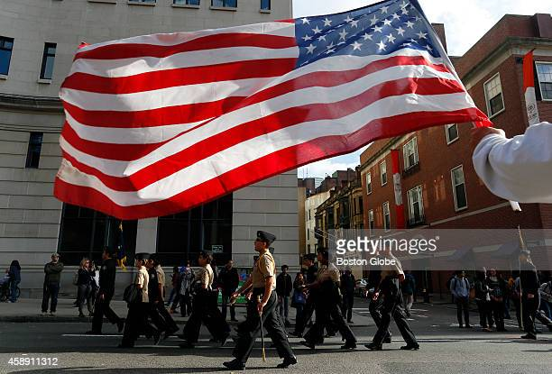 A man along the parade route holds an American flag as the Veterans Day Parade passes by in Boston on November 11 2014