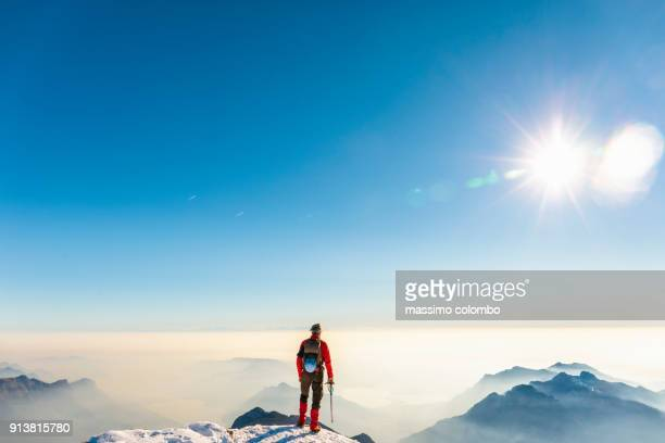 man alpinist on top of the mountain - horizonte fotografías e imágenes de stock