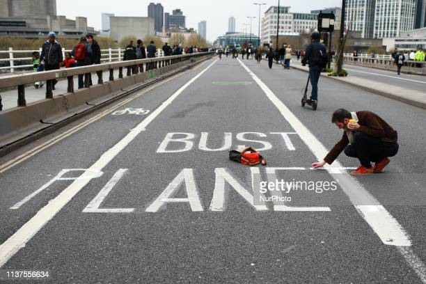 A man alters markings for a bus lane to read 'Bust Planet' along the road from members and supporters of climate change activist group Extinction...